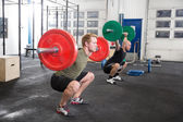 Team trains squats at fitness gym center — Stock Photo