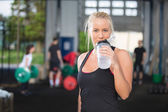 Woman drinking water at fitness gym center — Stock Photo