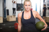 Fitness woman with slam ball at gym center — Stockfoto