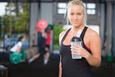 Woman rest and drinking water at fitness gym — Stock Photo