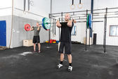 Clean and jerk workout at fitness gym center — Stock Photo