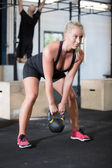 Woman trains with kettlebell in fitness gym — Stock Photo
