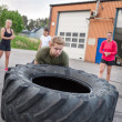 Young man flipping heavy tires outdoor — Stock Photo