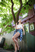 Attractive blonde teenage girl and wooden house — Stockfoto