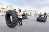 Fitness team flipping heavy tires as workout — Stock Photo