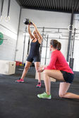 Woman lift kettlebells with personal trainer — Stockfoto