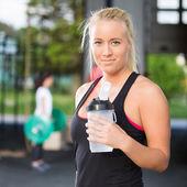 Resto de mulher e água potável após treino — Fotografia Stock