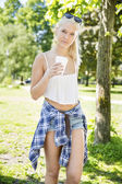 Beautiful teenage girl drinking coffee in park — Stock Photo