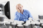 Overworked and exhausted businessman at office — Stock Photo