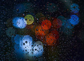 Blurred light with rain drops on the window — Stock Photo