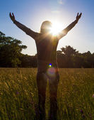 Young girl spreading hands with joy and inspiration facing the sun,sun greeting — Stock Photo