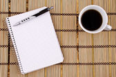 Kladblok, pen en koffie beker. — Stockfoto