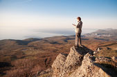 Man with mobile phone on the top of world — Stockfoto
