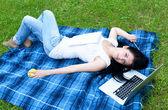 молодая женщина, используя ноутбук в парке — Стоковое фото