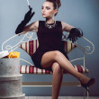 Young luxurious rich girl in black dress sitting on a sofa holding cigarette holder with cigarette in hand with long gloves and jewelry or ornaments, next to the box for hats in the studio — Stock Photo