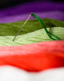 Variegated threads and needle — Stock Photo