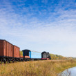 Old train moving away near creek — Stock Photo