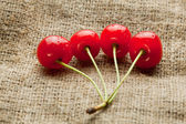 Red cherry bunch on hessian background — Stock Photo