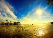 Sun star at morning on receding sea shore — Stock Photo