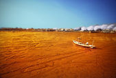 Wrecked boat at receding shore — Stock Photo