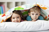 Cheerful brother and sister under blanket — Stok fotoğraf