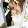 Wedding kiss into the car — Stock Photo