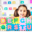 Schoolgirl with Alphabet Puzzle — Stock Photo