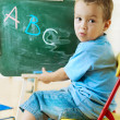 Little schoolboy at the chalkboard — Stock Photo