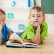 Two little boys reading books on the floor — Foto Stock
