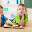 Two little boys reading books on the floor — Stock Photo