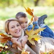 Mother and son enjoying autumn in park — Stock Photo