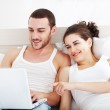 Couple Relaxing in Bed and Looking at a Laptop — Stock Photo