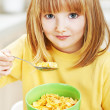 Stock Photo: Little girl eating cornflakes for breakfast