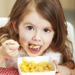 Beautiful little girl with cornflakes — Stock Photo #29609235
