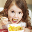 Beautiful little girl with cornflakes — Stock Photo