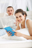 Young couple reading a book in bedroom — Stock Photo