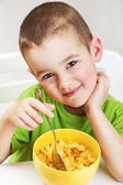 Boy eating cornflakes for breakfast — Stock Photo