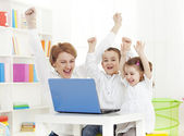 Mother using laptop with her children — Stock Photo
