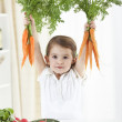 Cute girl holding carrots — Stock Photo #29831155