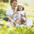 Happy family sitting on flowers field — Stock Photo