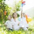 Mother and children playing with pinwheel — Stock Photo