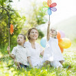 Stock Photo: Mother and children playing with pinwheel