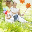 Stock Photo: Mother and son playing with pinwheel