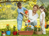 Mother and two children gardening — Stock Photo