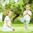 Yoga in park. mother and son — Stock Photo