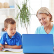 Mother working on laptop, son doing homework — Stock Photo