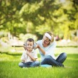 Mother and son in park, sitting on grass — Stock Photo #31118527