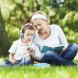 Mother and son in park, sitting on grass — Stock Photo #31118535
