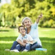 Mother resting with son in park — Stock Photo #31118537
