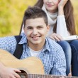 Two teenagers resting in the park, boy playing on guitar — Stock Photo